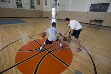 Decerega, right, instructing Brandon Milligan, is a trainer at One on One Basketball.